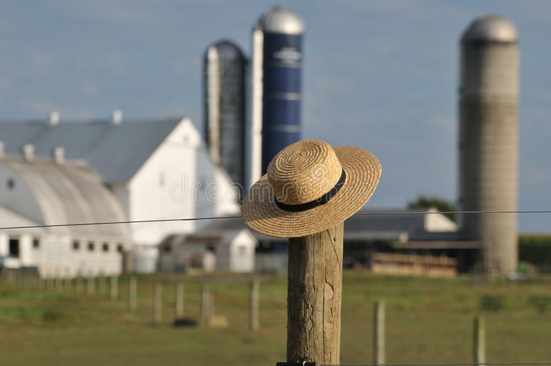 Amish farm with straw hat over fence post stock photos
