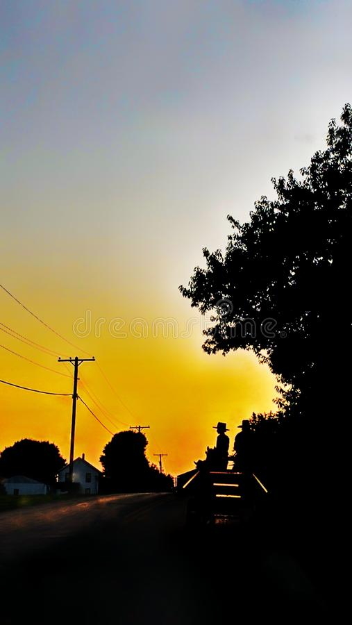Amish silohuette at sunset. The shape of Amish men driving a work wagon contrast against a colorful sunset stock photography