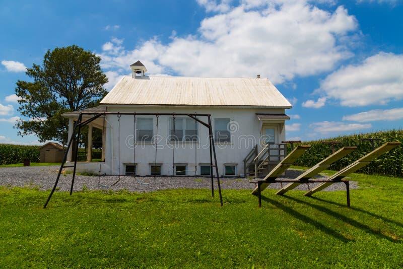 Amish szkoły dom z huśtawkami i seesaw fotografia royalty free