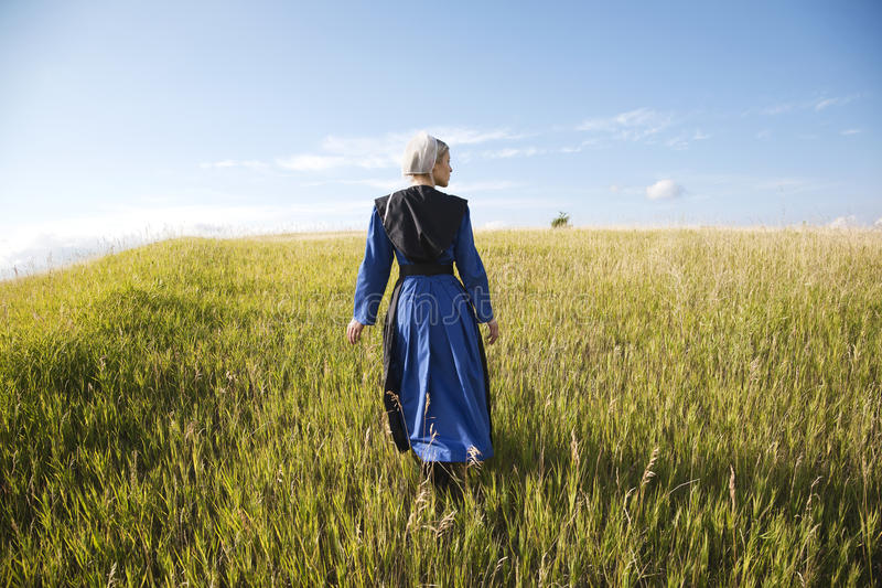 Amish woman in blue dress and black cape in field royalty free stock photography