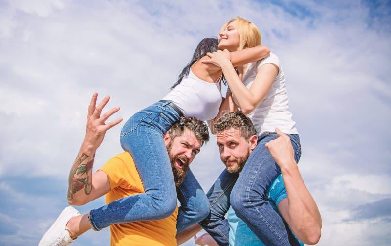 Amistad de familias Pares en el amor que se divierte Los hombres llevan a novias en hombros Vacaciones y diversi?n de verano pare fotografía de archivo libre de regalías