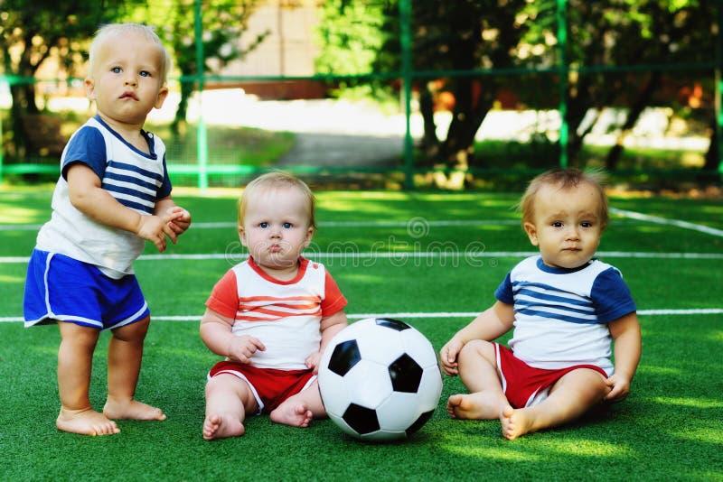 Amistad de los niños: tres niños en la tierra de deportes con el balón de fútbol Equipo de fútbol minúsculo que aprende jugar y c imagen de archivo