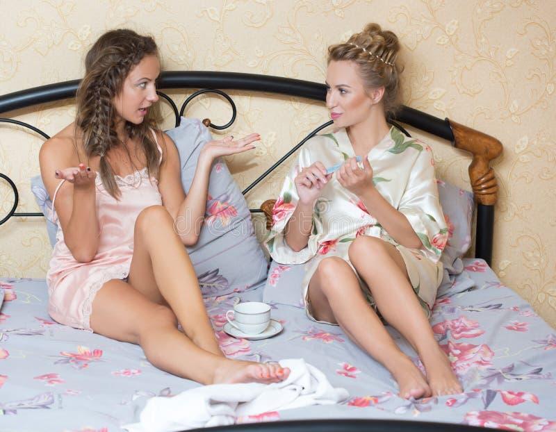 Amistad - dos muchachas sonrientes tienen chisme, blanco fotografía de archivo
