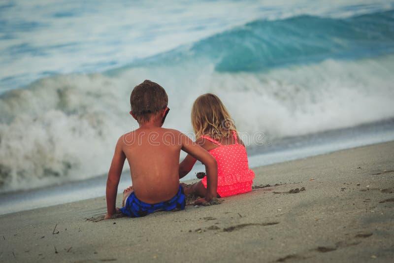 Amistad, niño pequeño de las vacaciones de la playa de la familia y muchacha mirando el mar imagen de archivo