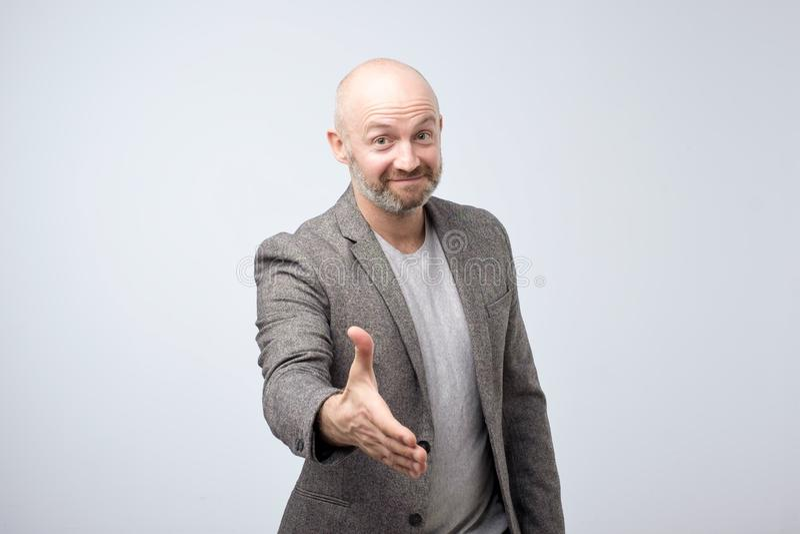 Amistoso-mirada del hombre europeo atractivo que da una mano en hola gesto mientras que sonríe alegre foto de archivo