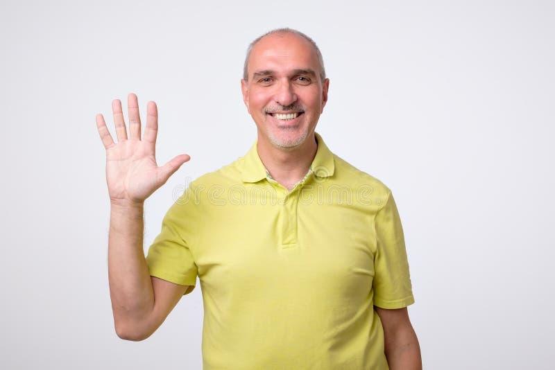Amistoso-mirada del hombre europeo atractivo que renuncia la mano en hola gesto mientras que sonríe alegre fotos de archivo