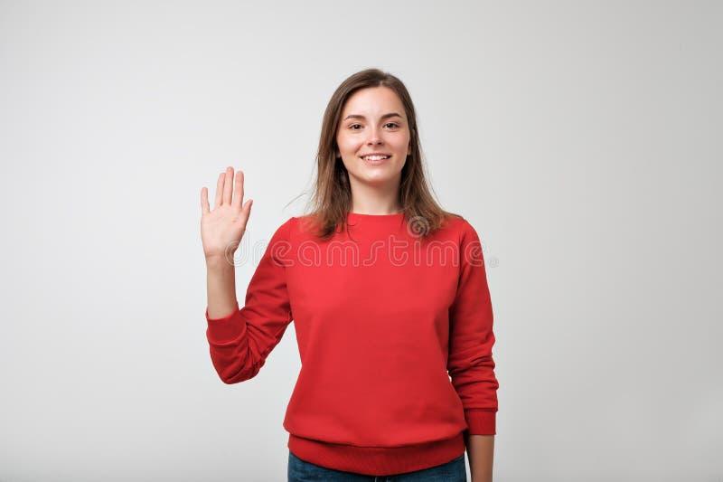 Amistoso-mirando al adolescente europeo se vistió en pulover rojo que decía el hola, agitando su mano fotografía de archivo