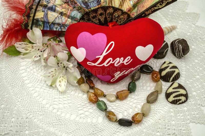Amivi su cuore, sulle perle, sul cioccolato, sul fan e sui fiori rossi su un tovagliolo openwork bianco immagini stock libere da diritti