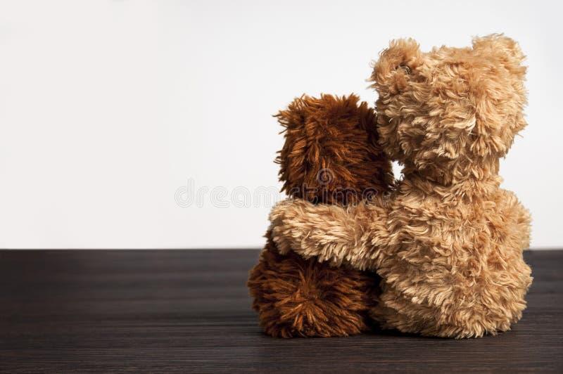 Amizade 2 ursos de peluche que realizam em um \ 'braço de s fotografia de stock