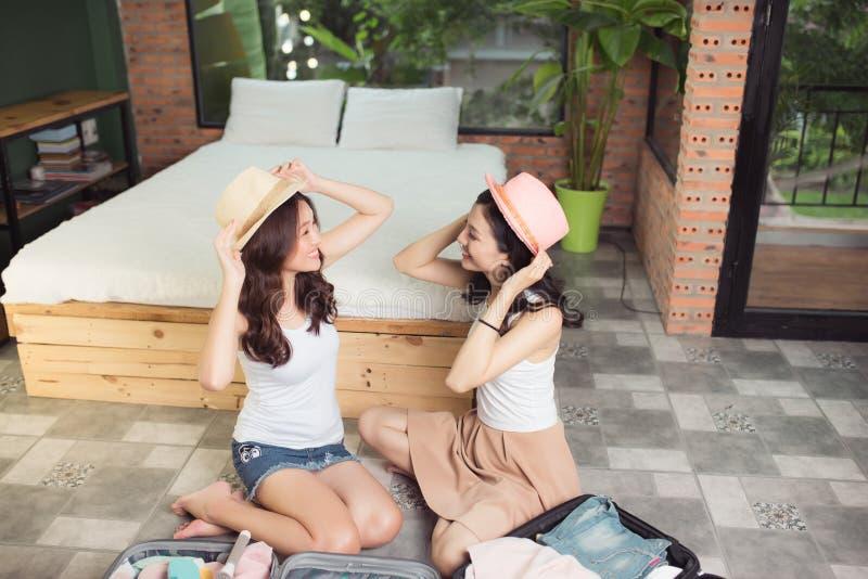 Amizade Curso Dois amigos asiáticos da jovem mulher que embalam um trav imagens de stock