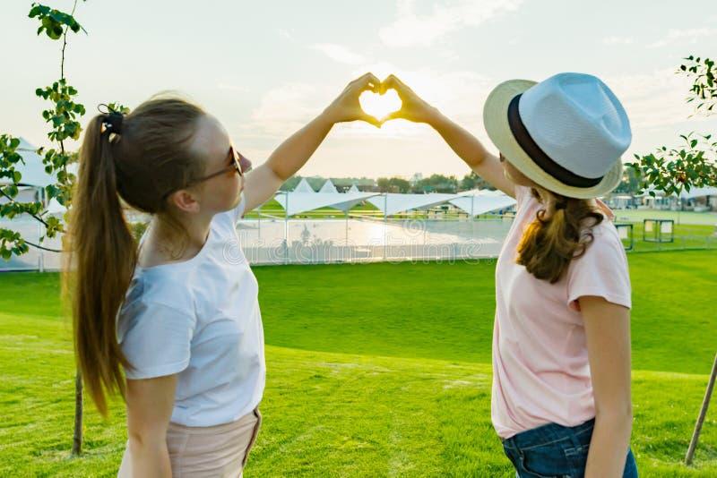 A amizade de dois adolescentes, as melhores amigas tem o divertimento na natureza, no gramado verde do parque e do entretenimento imagens de stock royalty free