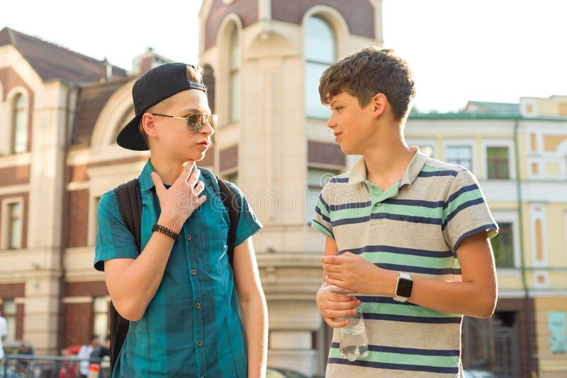 A amizade e a comunicação de dois adolescentes são 13, 14 anos velhos, fundo da rua da cidade imagem de stock