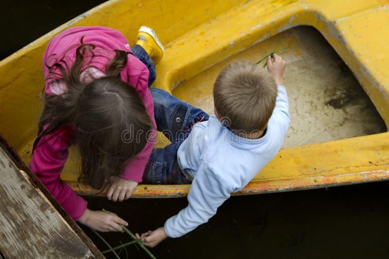 Amizade. miúdos que jogam no barco foto de stock
