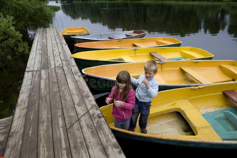 Amizade. miúdos que jogam no barco imagens de stock