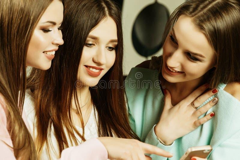 Amizade, povos e conceito da tecnologia - amigos ou adolescentes felizes com o smartphone no hom foto de stock royalty free