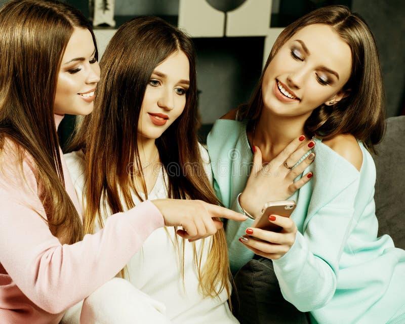 Amizade, povos e conceito da tecnologia - amigos ou adolescentes felizes com o smartphone no hom foto de stock