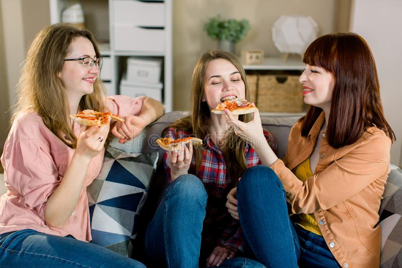 Amizade, povos, partido de pijama e conceito da comida lixo - três mulheres ou meninas novas felizes que comem a pizza, pipoca e imagem de stock