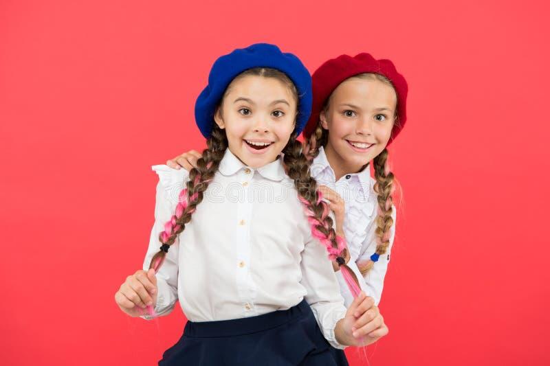 A amizade significa o apoio Melhores amigos das meninas no fundo vermelho Estudantes brincalhão bonitos das irmãs que têm o diver imagem de stock royalty free