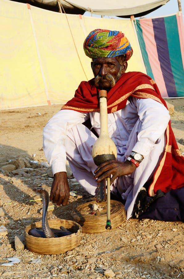 Ammaliatore di serpente del nomade che gioca pungi al mela del cammello, Pushkar, India fotografia stock