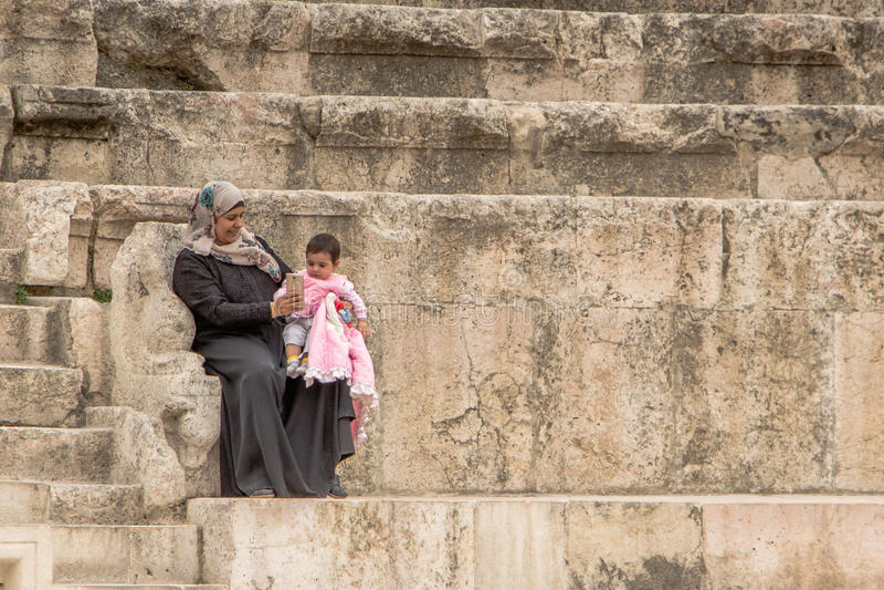 AMMAN, JORDAN - MAY 03, 2016: Young Arabic woman selfi. AMMAN, JORDAN - MAY 03, 2016: Young Arabic woman showing a selfie to her little daughter royalty free stock photography