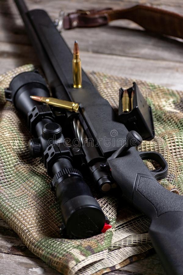 The Ammo with black bolt action rifle and scope on the multicam background. Close up stock photography