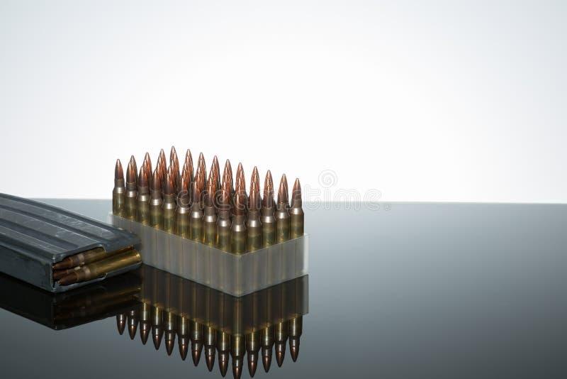 .223 ammo 50 count. Ammo .223 caliber magazine on reflective surface white background stock photos