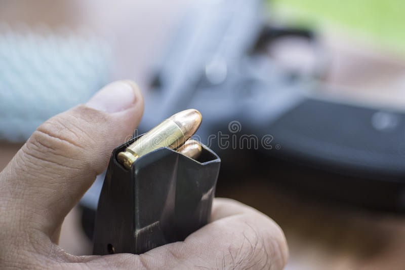 Ammo för påfyllning 9mm i pistolgemslutet upp Händer, kulor, tidskrift och handeldvapen fotografering för bildbyråer