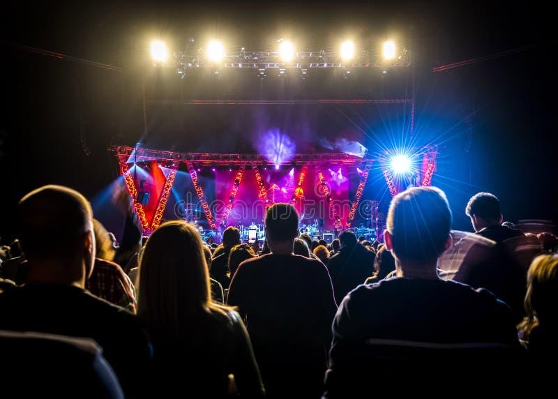 Ammucchi al concerto di musica, siluette della gente backlit dalle luci della fase fotografie stock libere da diritti