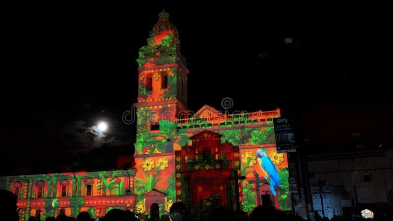Ammucchi ammirando lo spettacolo delle luci sporgenti sulla facciata della chiesa di Santo Domingo, nel centro storico di Quito fotografia stock libera da diritti