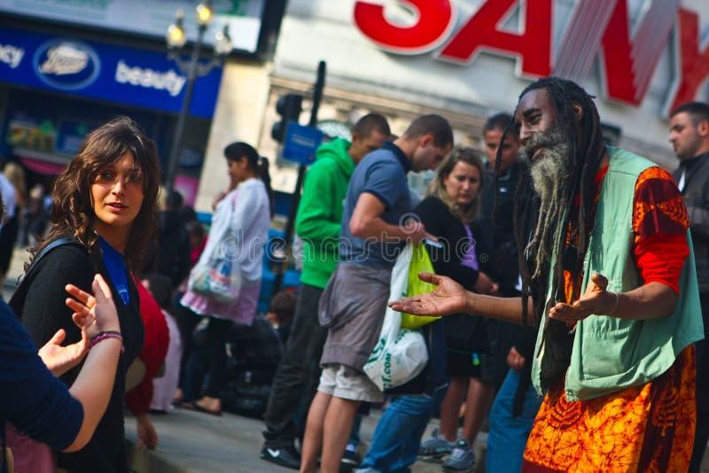 Ammucchi esaminando l'artista della via sul circo di Piccadilly fotografia stock libera da diritti