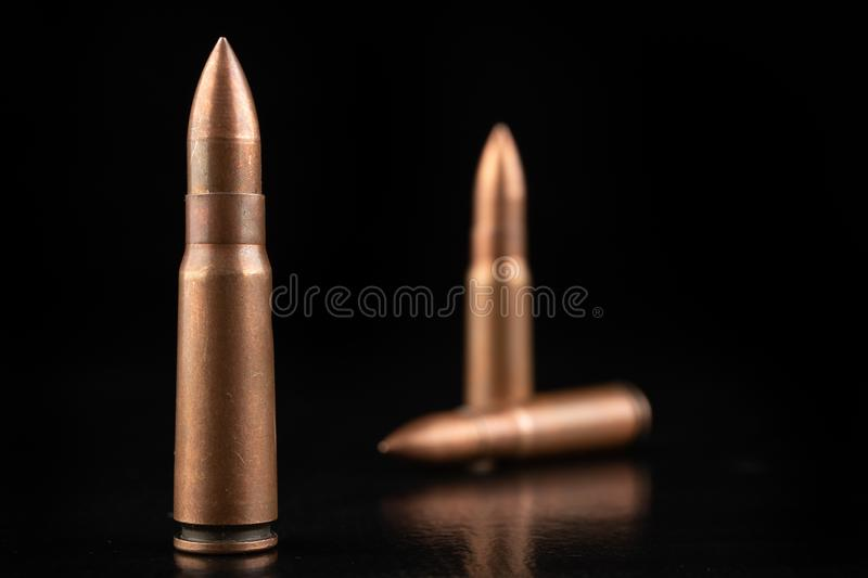Ammunition of a high-speed rifle. Cartridges for a military rifle. Dark background, ammo, armed, army, battle, black, brass, bullet, bullets, caliber, closeup stock photography