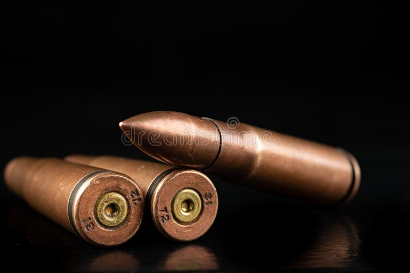 Ammunition of a high-speed rifle. Cartridges for a military rifle. Dark background, ammo, armed, army, battle, black, brass, bullet, bullets, caliber, closeup royalty free stock images