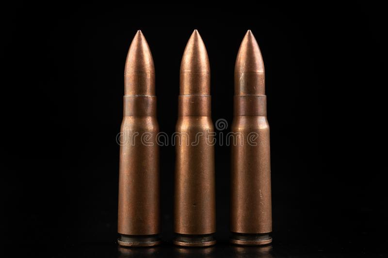 Ammunition of a high-speed rifle. Cartridges for a military rifle. Dark background, ammo, armed, army, battle, black, brass, bullet, bullets, caliber, closeup stock image