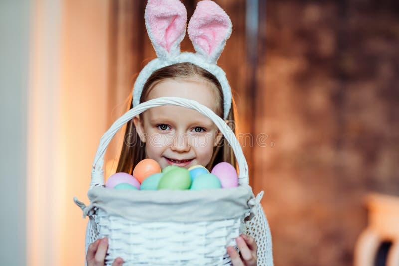 Amo celebrar Pascua Cesta linda de la tenencia de la muchacha con los huevos y la sonrisa de Pascua Concepto de la celebración imagenes de archivo