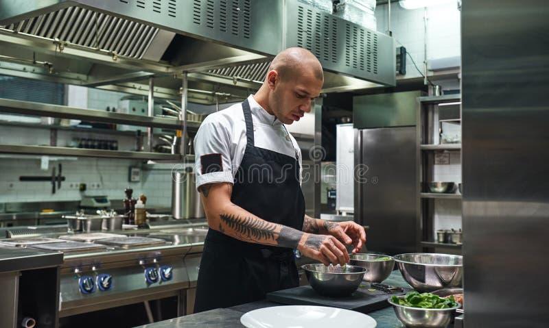 Amo cucinare Cuoco unico maschio in grembiule, con i tatuaggi neri sulle sue armi che preparano insalata in una cucina del ristor fotografie stock libere da diritti