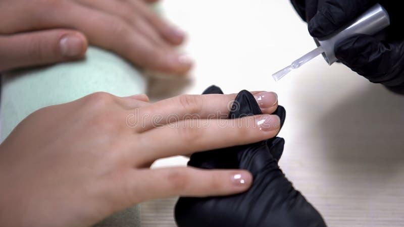 Amo de la manicura que aplica la base del clavo antes del esmalte de uñas, procedimiento del salón de belleza foto de archivo libre de regalías