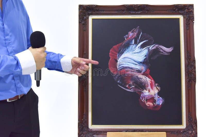 Amo de las ceremonias que hablan en pescados de la exposición con el pictur de los pescados foto de archivo