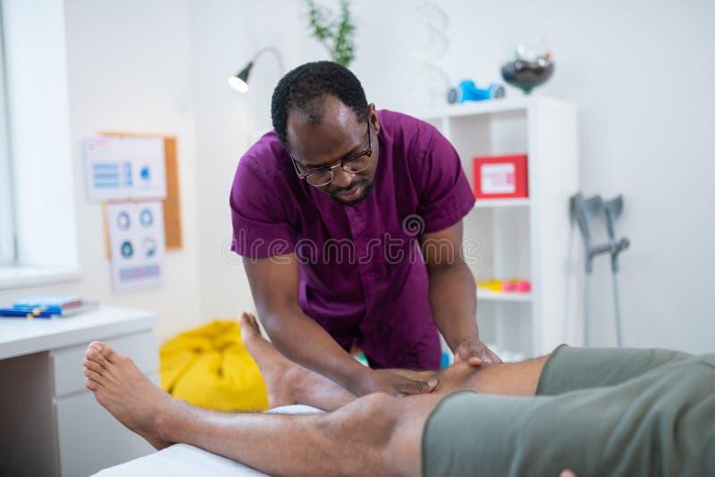 Amo de piel morena del masaje que da masajes a las rodillas para el hombre fotos de archivo libres de regalías