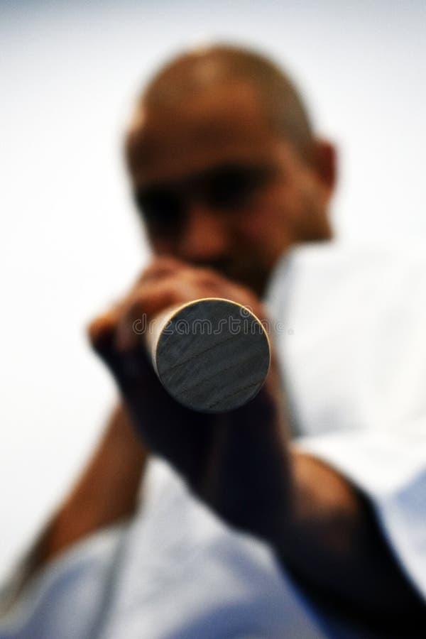 Amo del Aikido con el jo listo para apuñalar imágenes de archivo libres de regalías