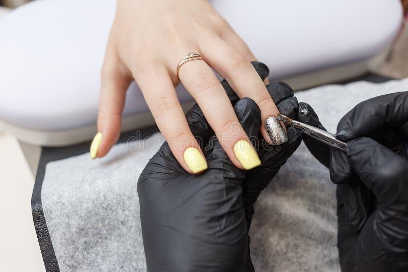 Amo del clavo que lleva los guantes negros que aplican el cepillo en clavos de acrílico en el salón Primer en manicura foto de archivo libre de regalías