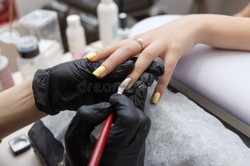 Amo del clavo que lleva los guantes negros que aplican el cepillo en clavos de acrílico en el salón Primer en manicura foto de archivo