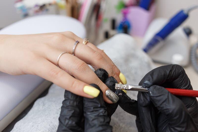 Amo del clavo que lleva los guantes negros que aplican el cepillo en clavos de acrílico en el salón Primer en manicura fotos de archivo