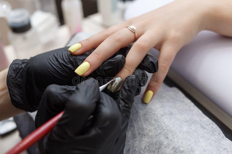 Amo del clavo que lleva los guantes negros que aplican el cepillo en clavos de acrílico en el salón Primer en manicura imágenes de archivo libres de regalías
