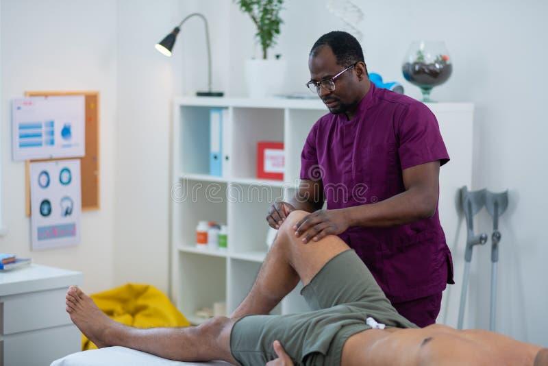 Amo del masaje en vidrios y la pierna de masaje uniforme para el hombre en pantalones cortos imágenes de archivo libres de regalías