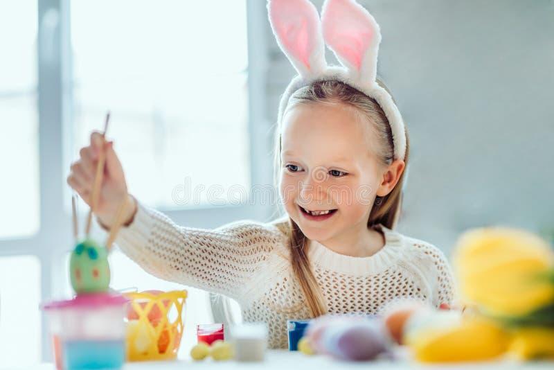 Amo dipingere le uova di Pasqua! La bambina in orecchie di coniglio dipinge le uova di Pasqua fotografie stock