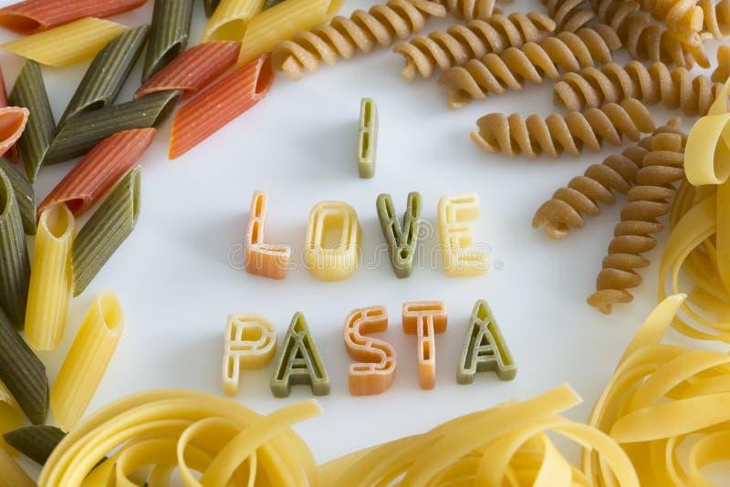 Amo el texto de las pastas en la placa blanca con las letras coloridas de las pastas imagenes de archivo