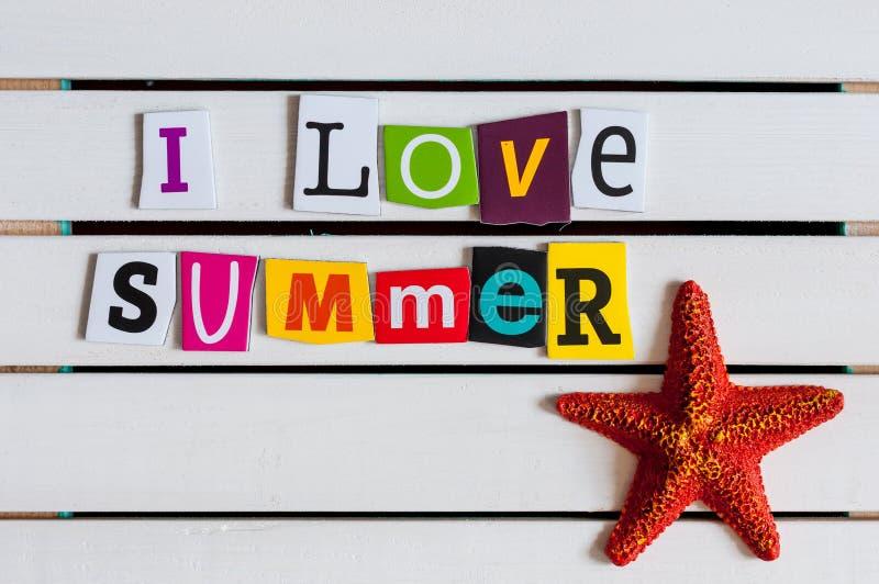 Amo el verano - escrito con recortes de la letra de la revista del color en el tablero de madera concepto del recorrido fotografía de archivo