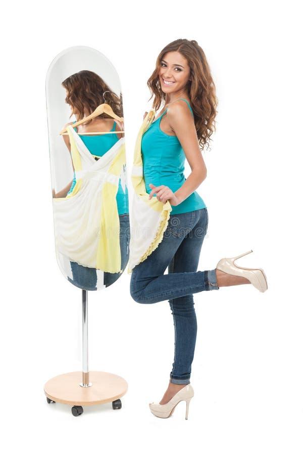 ¡Amo este vestido! Mujeres jovenes felices que sostienen un vestido mientras que soporte fotografía de archivo libre de regalías