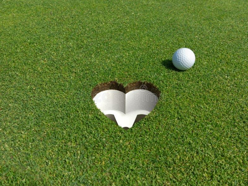 Amo il golfball ed il foro del golf con la forma del cuore di e immagine stock libera da diritti