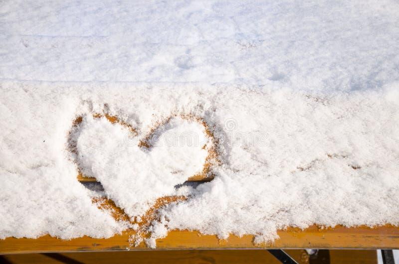 Amo invierno: Un corazón en la nieve foto de archivo